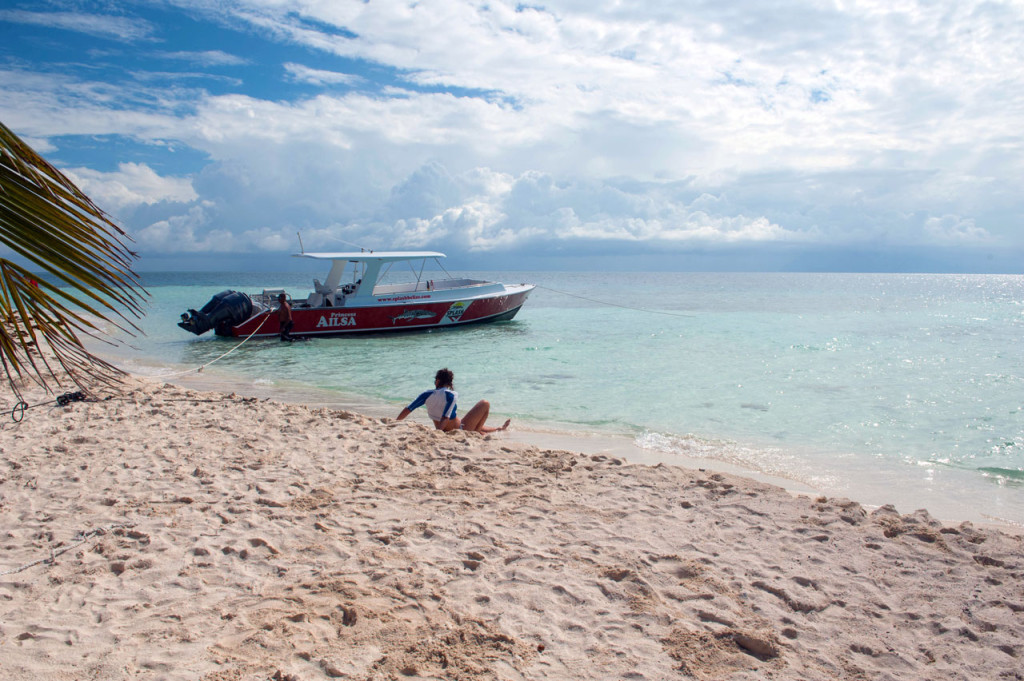 A person in a rash guard sits on the sand with a boat anchored just off-shore.