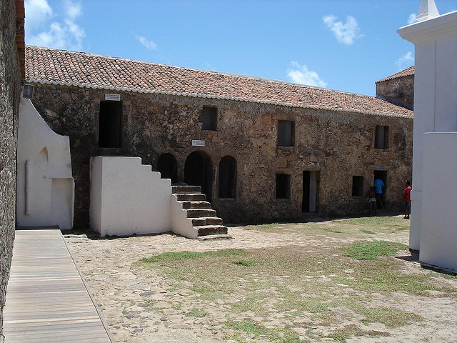 Courtyard view of stone buildings with clay tiled rooves.