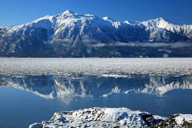 Snow-capped mountains reflect in water covered in melting ice.