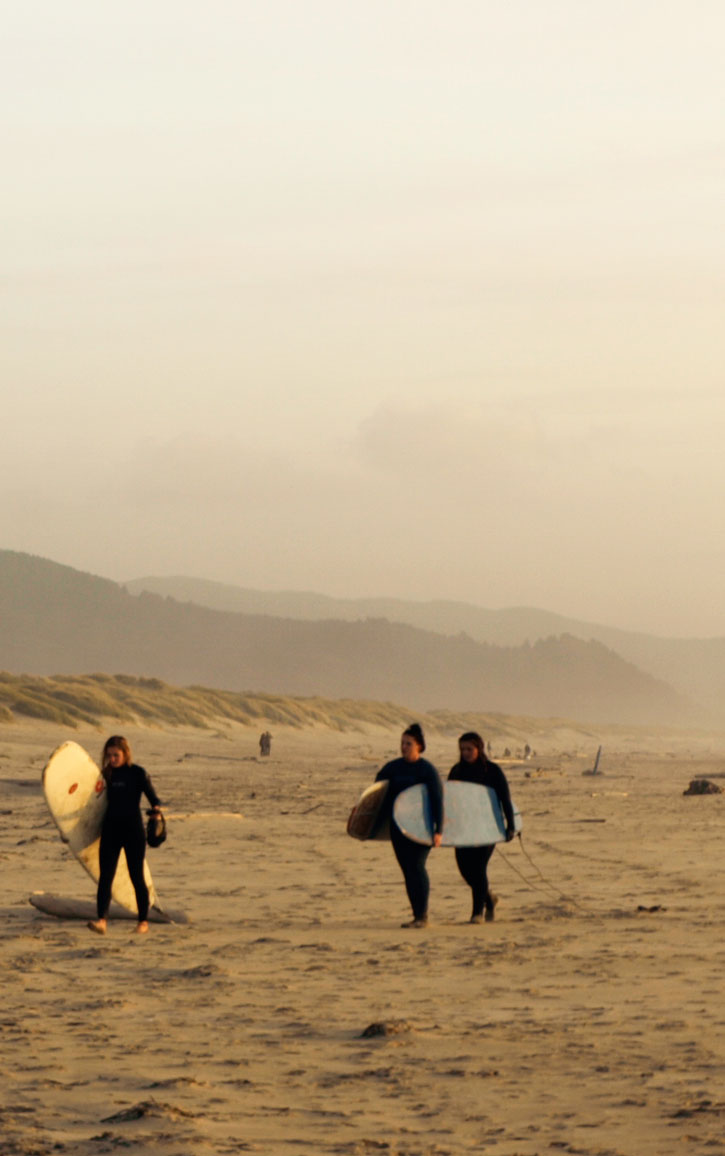 A trio of surfers carrying longboards cross the sand.
