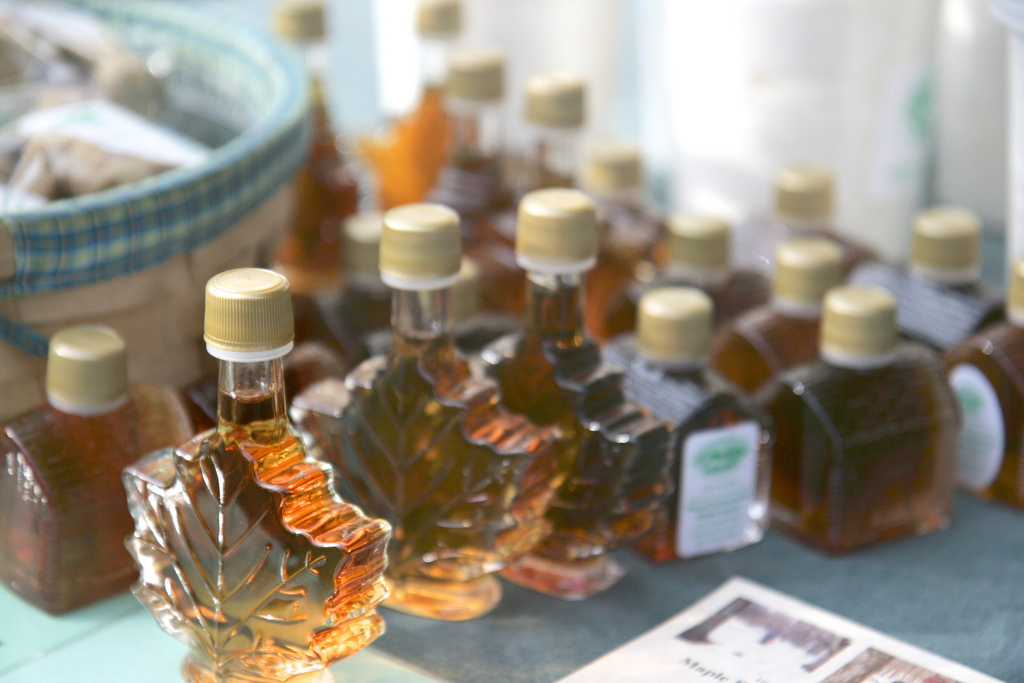 Small bottles of maple syrup shaped like leaves are for sale at a farmers market table.