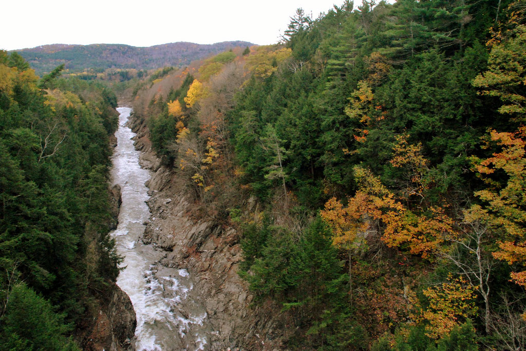 A narrow river rushes through a steep canyon lined with trees turning golden in Queechee.
