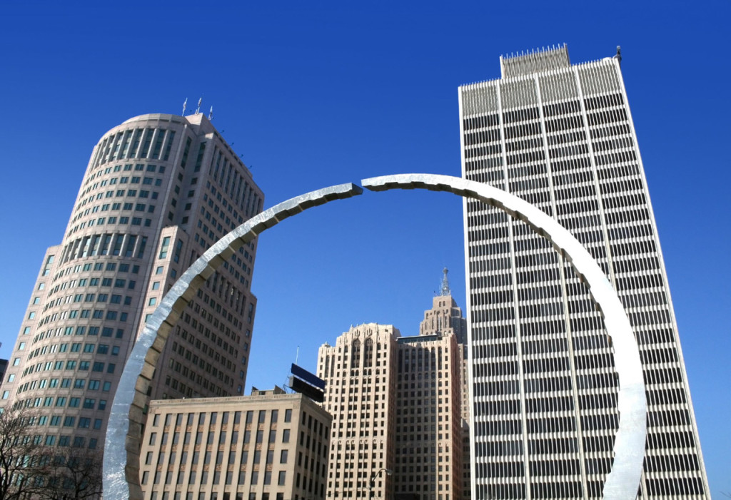 Looking up at a nearly round arch steel sculpture and skyscrapers in downtown Detroit on a perfectly clear day.
