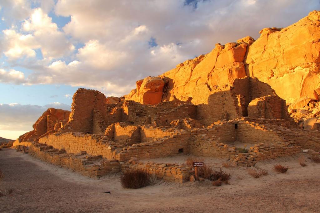 Afternoon sun turns the rocks orange behind the remains of Pueblo ruins.
