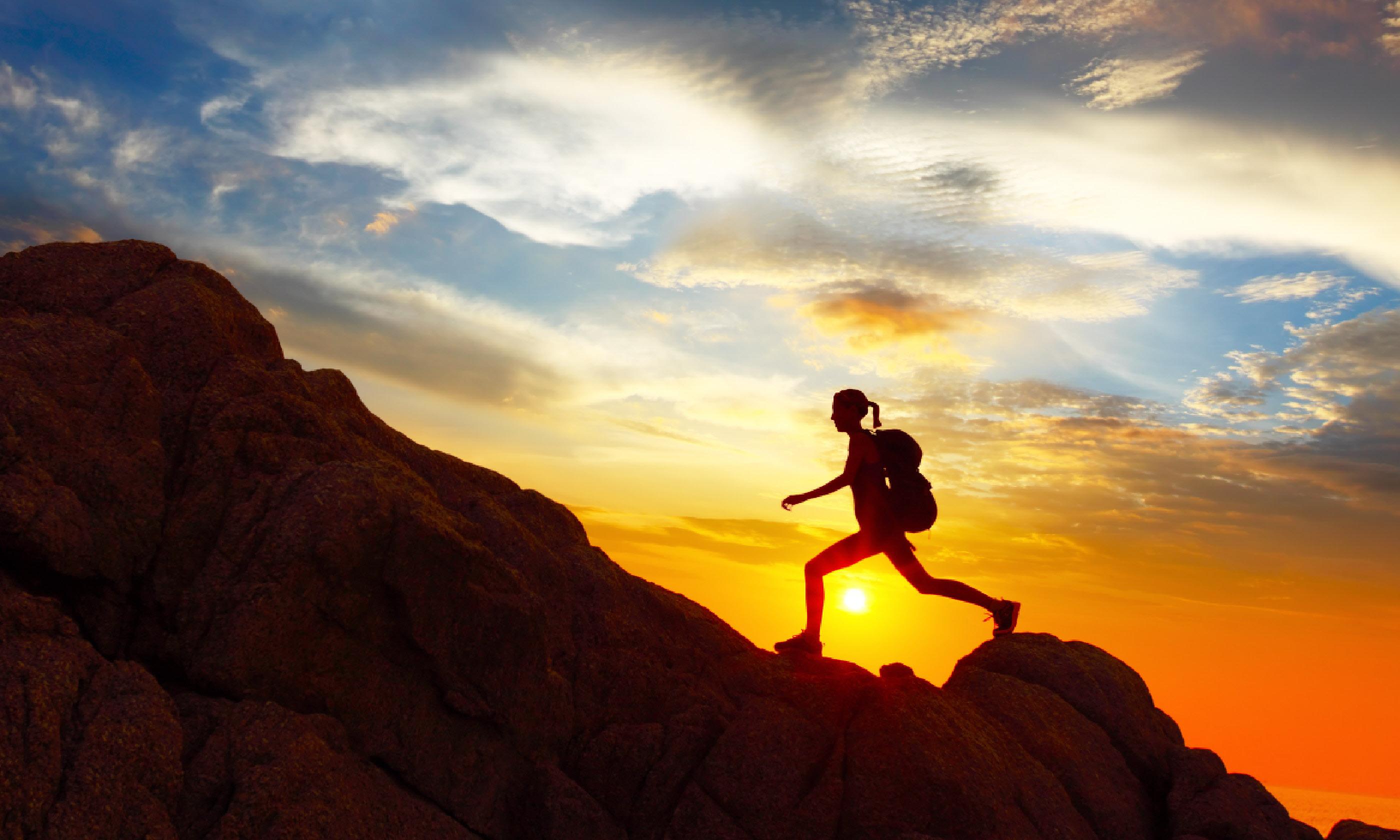 Hiker with backpack crossing rocky terrain (Shutterstock: see credit below)